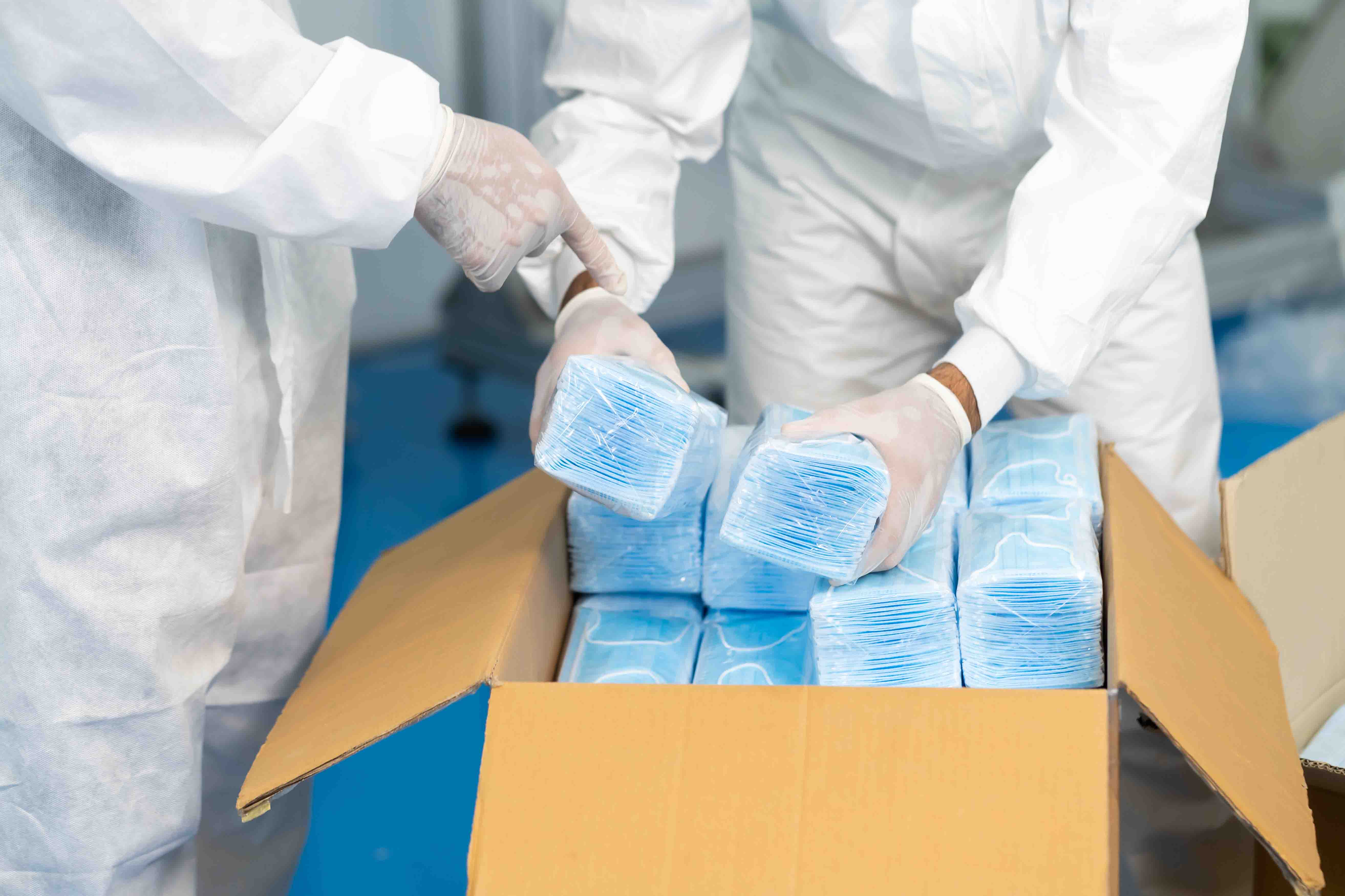 Workers are packing masks in boxes for delivery to customers.